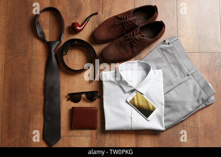 Flat lay set of male clothes and accessories on wooden background - Stock Photo