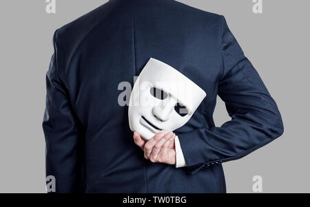 Business fraud concept. Businessman hide the mask in hand behind his back. - Stock Photo