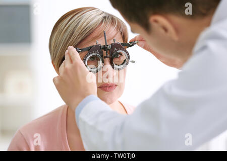 Ophthalmologist examining eyes of mature woman in clinic, closeup - Stock Photo
