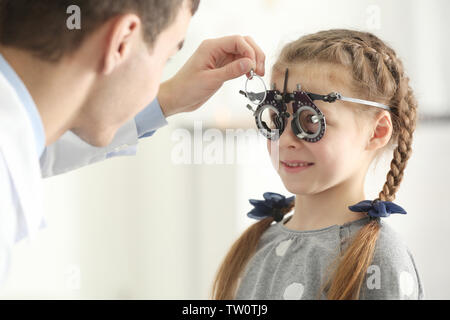 Ophthalmologist examining eyes of little girl in clinic - Stock Photo