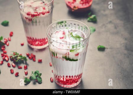 Two glasses of cold fruit cocktail on gray background - Stock Photo