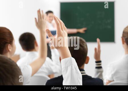 Schoolchildren raising hands for answer during lesson - Stock Photo