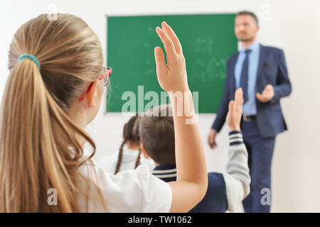 Schoolgirl raising hand for answer during lesson - Stock Photo