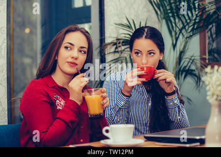 Image of a two happy girls friends sitting in cafe talking with each other drinking coffee, pointing to someone. - Stock Photo