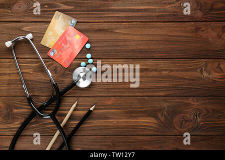 Medical concept. Stethoscope, pills and credit cards on wooden background - Stock Photo