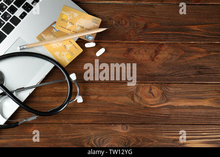 Laptop, stethoscope, pills and credit cards on wooden background - Stock Photo