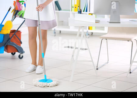 Chambermaid cleaning floor in office - Stock Photo
