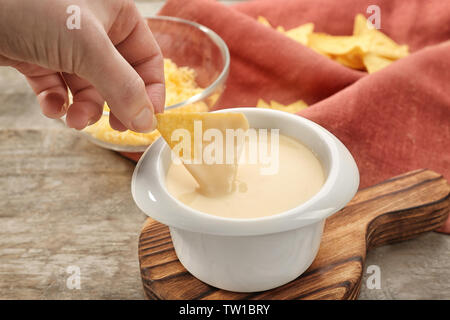 Female hand dipping nacho in bowl with beer cheese dip, closeup - Stock Photo