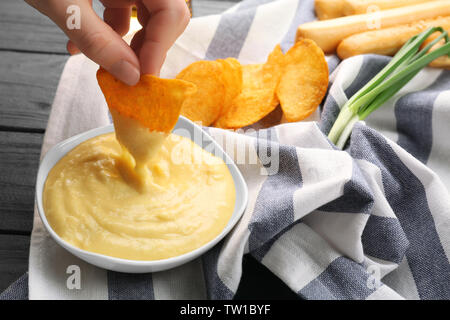 Woman hand dipping nacho in beer cheese dip - Stock Photo