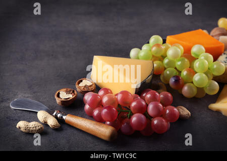 Sorts of cheese, grape and nuts on grey background - Stock Photo
