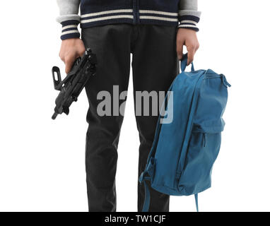 Teenage boy with backpack holding gun on white background - Stock Photo
