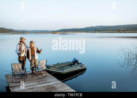Grandfather with adult son standing together on the wooden pier, enjoying the sunrise while fishing on the lake early in the morning - Stock Photo