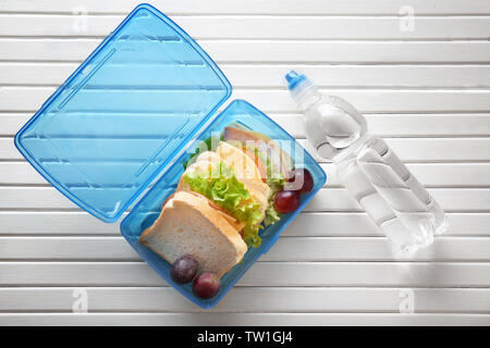 Lunchbox and bottle of water on wooden background - Stock Photo