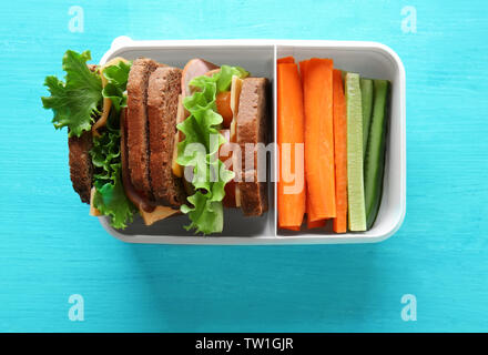 Healthy school lunch in plastic box on blue wooden table - Stock Photo