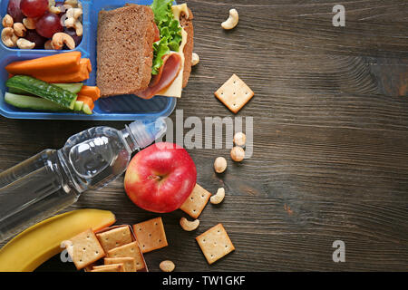 Lunchbox with sandwich and different products on wooden background - Stock Photo