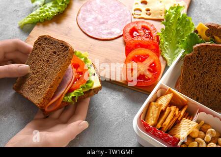 Woman making tasty sandwich on table - Stock Photo
