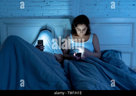 Sad man and woman married couple using their smart mobile phone in bed at night ignoring each other as strangers in relationship and communication pro - Stock Photo