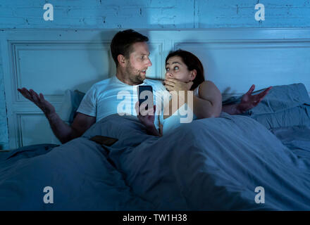 Angry man husband or boyfriend feeling jealous and betrayed by addicted to mobile phone wife girlfriend chatting online on phone to somebody in relati - Stock Photo