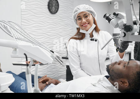 Beautiful female dentist looking at camera, smiling and posing while curing teeth of patient. Young woman working while african man lying on dentist chair in clinic. Concept of health and treatment. - Stock Photo
