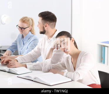 Tired young woman sleeping during conference in office - Stock Photo