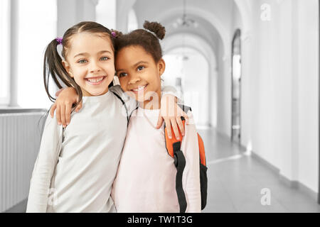 Portrait of two best friends little school girls standing at corridor, embracing each other and smiling. African and Caucasian girls studying together at school. Concept of friendship. - Stock Photo
