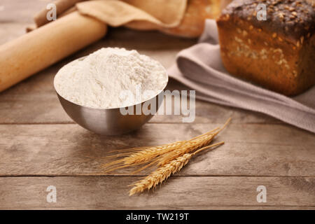 Bowl of white flour and wheat ears on wooden table - Stock Photo