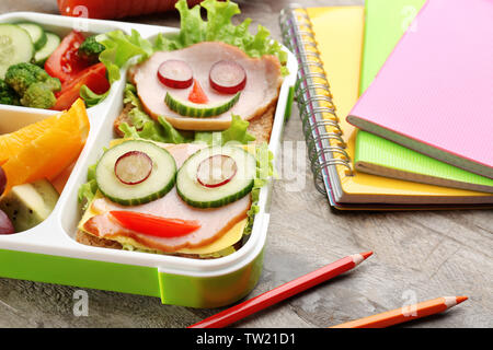 Funny sandwiches in lunch box and colorful stationery on wooden background - Stock Photo