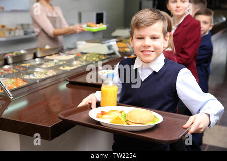 Cute girl holding tray with delicious food in school cafeteria - Stock Photo