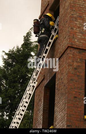 fire fighter climbing 13.5m ladder - Stock Photo