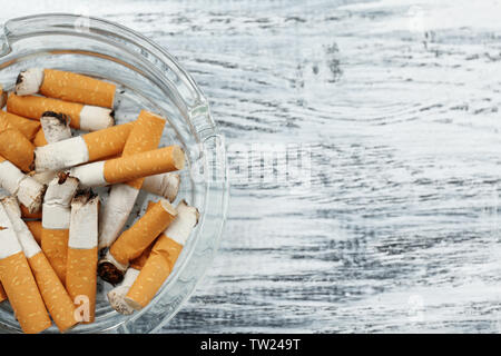 Glass ashtray with cigarette butts on wooden background - Stock Photo
