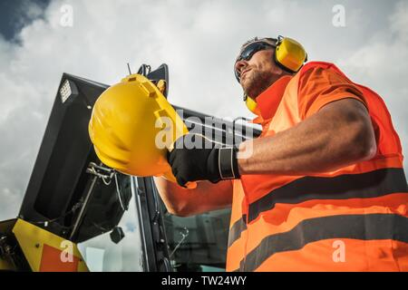 Caucasian Construction Contractor Wearing Protection Accessories. Hard Hat and Noise Reduction Headphones. - Stock Photo