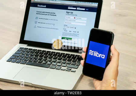 18 June 2019, Ljubljana Slovenia - Hand holding a smartphone with Libra logo on it, next to Facebook website opened on computer laptop - Stock Photo