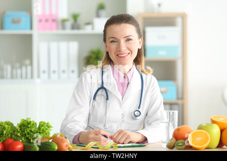 Young female nutritionist working in her office - Stock Photo