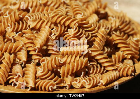 Wholemeal Fusilli in a plate. Integral Pasta over a wooden table . - Stock Photo