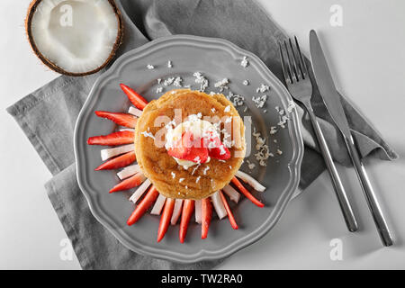 Stack of delicious coconut pancakes with strawberry and butter cream on white table - Stock Photo