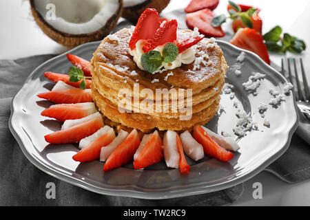 Stack of delicious coconut pancakes with strawberry and butter cream on napkin - Stock Photo
