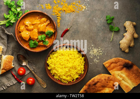 Chicken tikka masala with yellow rice and naan on a dark brown background. Indian food. Top view, copy space, flat lay Stock Photo