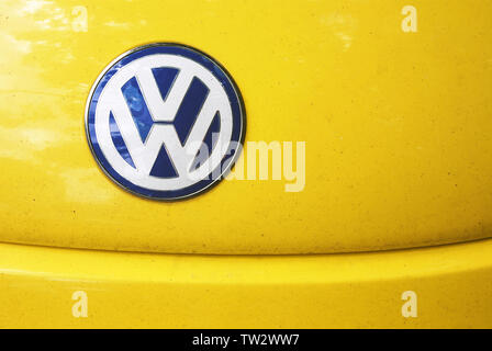 White and blue w symbol imitating Volkswagen icon on  shabby yellow hood of fake Chinese replica of Volkswagen Beetle car. - Stock Photo