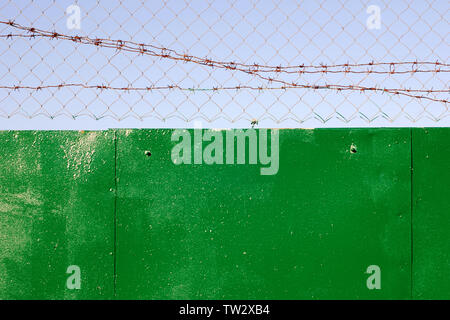 Fence topped with chain-link and barbed wire against clear sky, metal surface roughly painted with green paint - Stock Photo