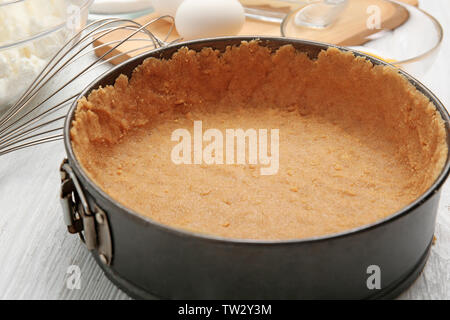 Baking form with base for cheesecake on table - Stock Photo