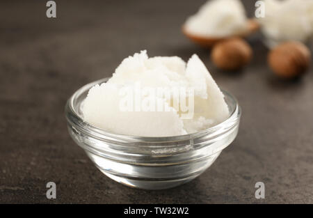 Shea butter in glass bowl on table, close up - Stock Photo