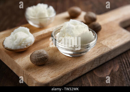 Shea butter in bowl and spoon on wooden background - Stock Photo