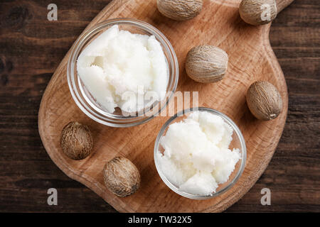 Shea butter in bowls on wooden background, top view - Stock Photo