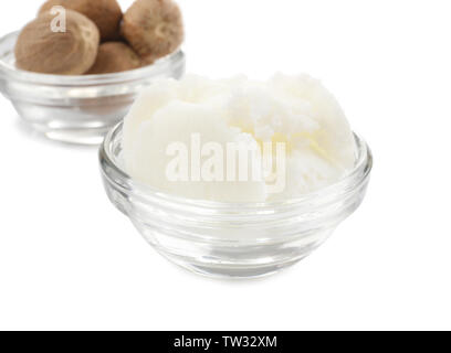 Shea butter and nuts in bowls on white background - Stock Photo