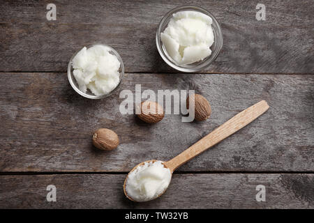 Shea butter in bowls and spoon on wooden background, top view - Stock Photo