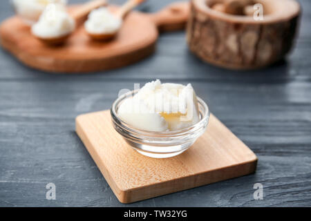 Shea butter in bowl on wooden background - Stock Photo