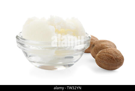 Shea butter in bowl and nuts isolated on white - Stock Photo