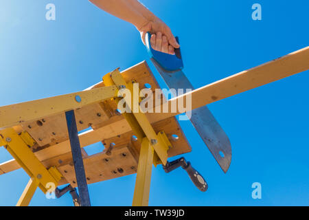 Close POV shot from below of a man's hands sawing the end off a piece of wood, which is clamped in a portable workbench, outside against a blue sky. - Stock Photo