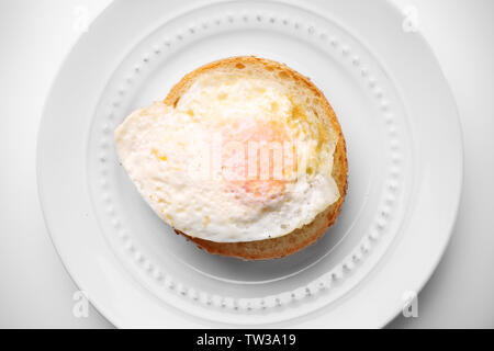 Ceramic plate with hamburger roll and over hard fried egg on light background - Stock Photo