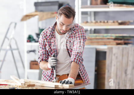 Carpenter pulling out nail from wooden plank in light workshop - Stock Photo